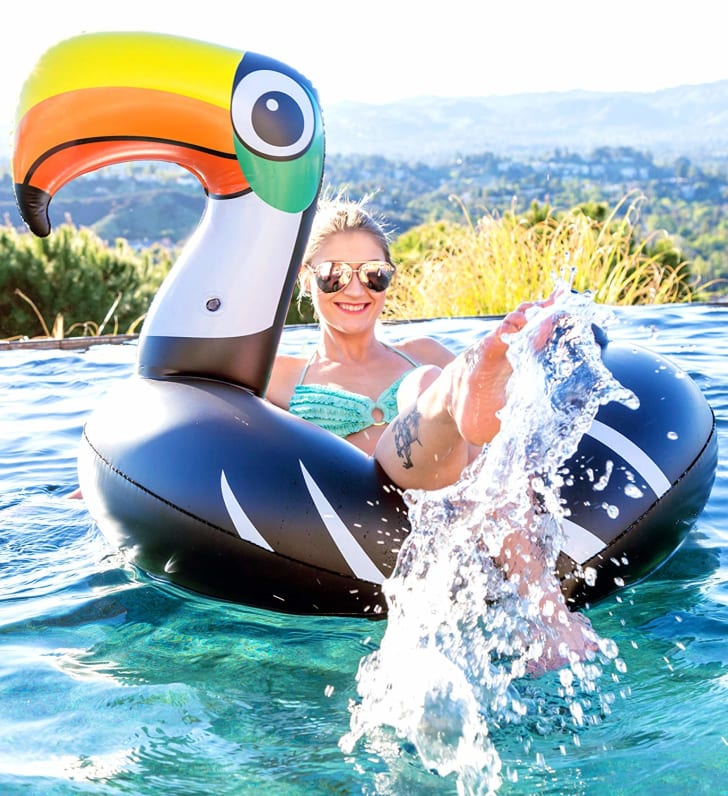 A woman in a pool on a toucan-shaped pool float