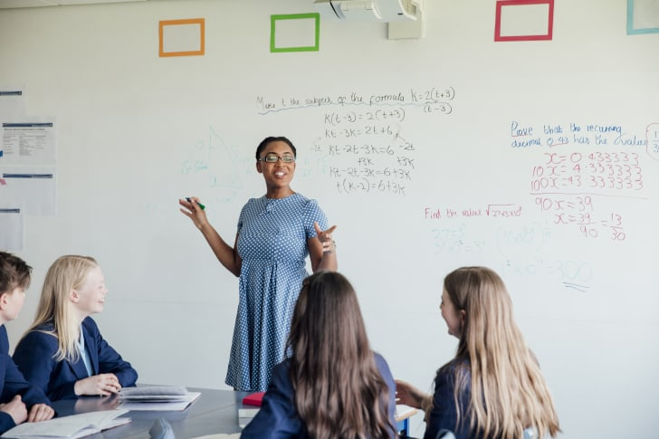 A young female teacher in front of a white board talking to a group of students