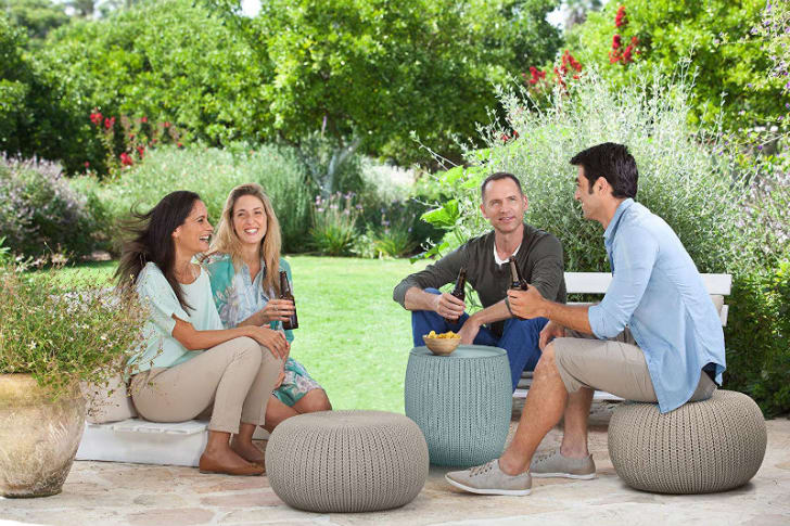 People on a patio rest on Keter's knit poufs.
