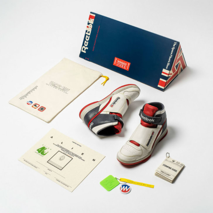 A pair of Reebok Alien Stomper sneakers and accessories