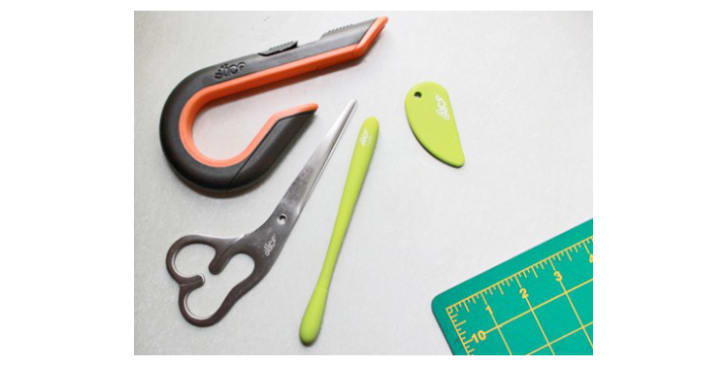 A box cutter, safety cutter, precision cutter, and scissors on a craft table