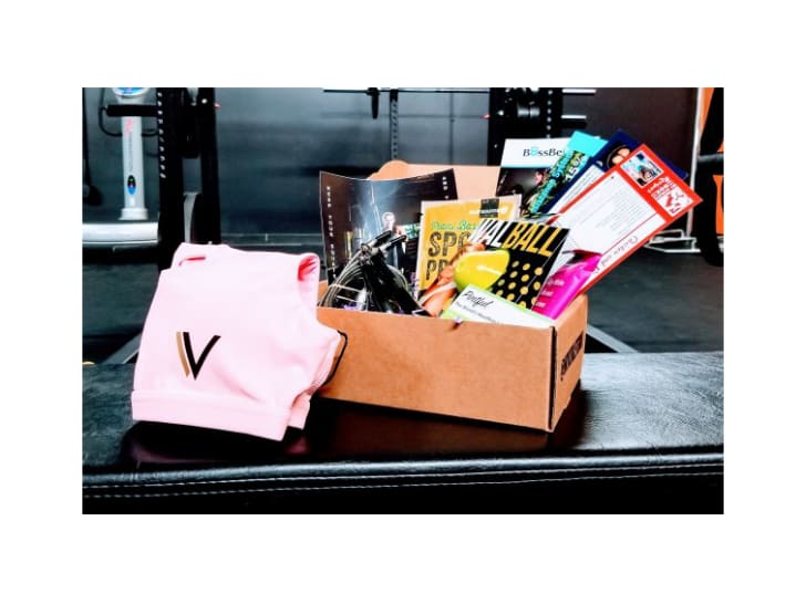 A subscription box filled with goods on a weight bench in a gym