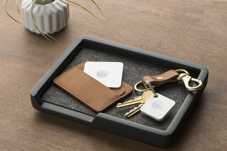 Tile trackers sitting in a tray inside a wallet and attached to a keychain.