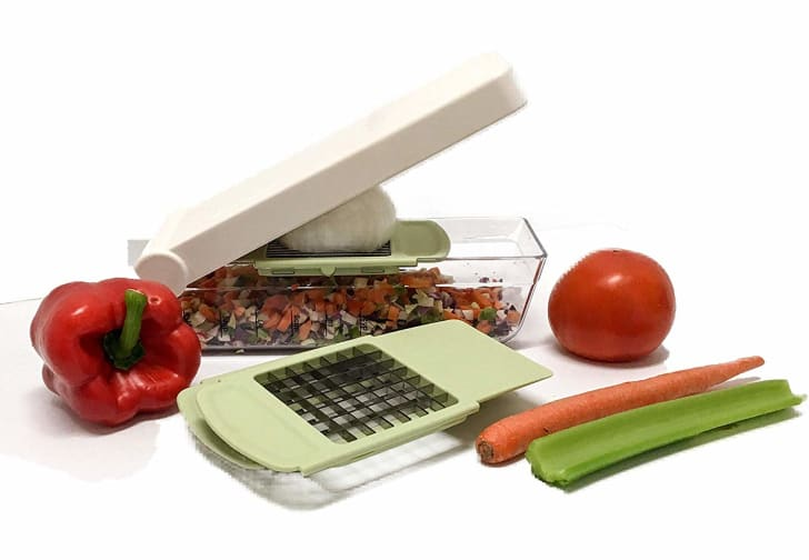 A Chop Wizard with an onion in it near a tomato, a red bell pepper, a carrot, and a stalk of celery