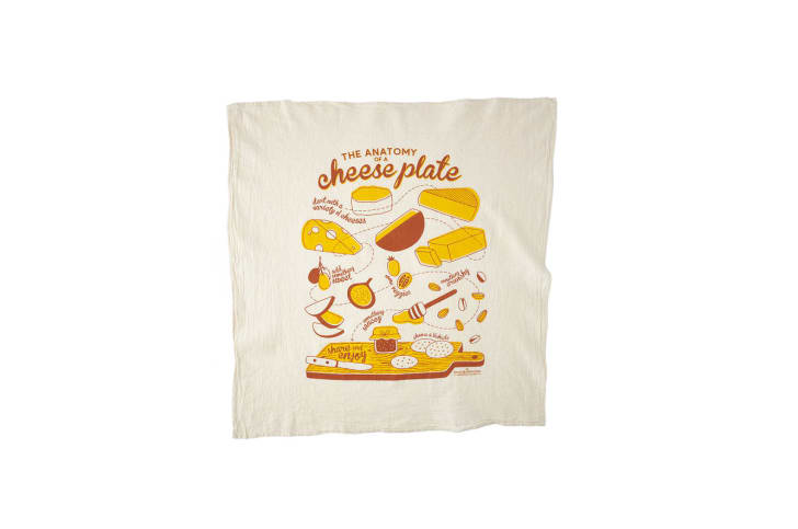 A dish towel with an illustration of cheeses and a cutting board on it