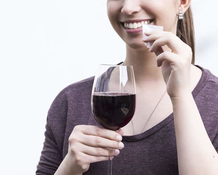 Woman with wine wiping teeth.