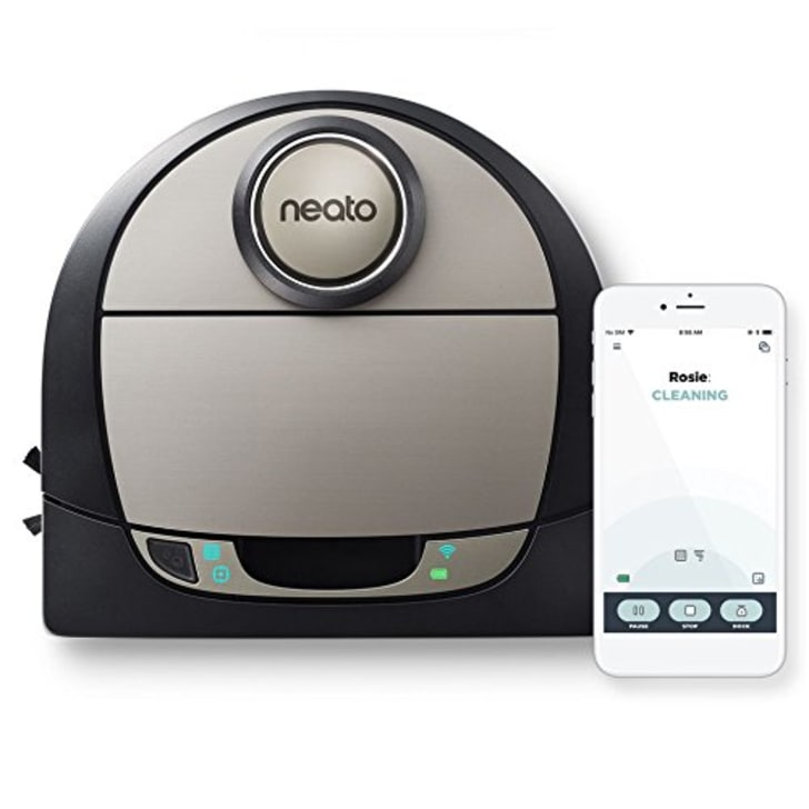 A Neato robot vacuum next to a smartphone open to the Neato app