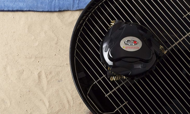 An automatic grill cleaning robot on a charcoal grill