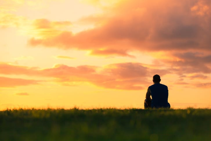 Man sits by himself watching the sunset