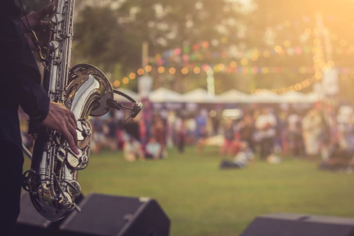 A saxophone player in front of a festival crowd seated on a lawn