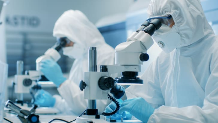 Two scientists in clean room suits look through microscopes