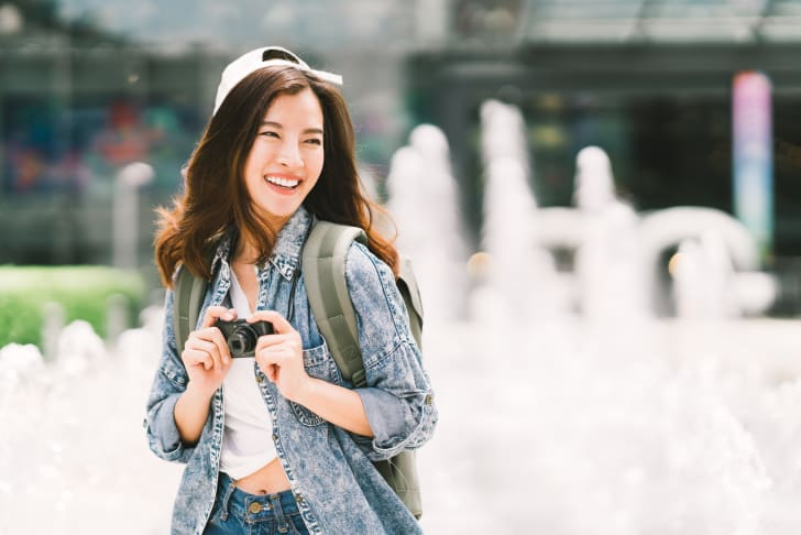 A young woman traveling with her camera and backpack
