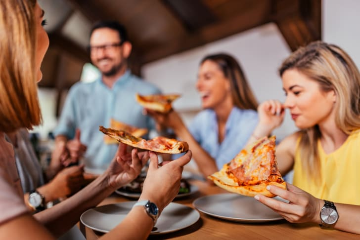 Close-up image of group of friends or colleagues eating pizza