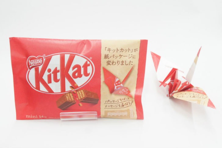 A KitKat candy bar package and origami wrapper are pictured