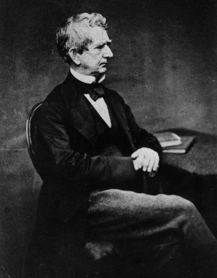 A black and white image of William H. Seward sitting with his hands clasped and his legs crossed.