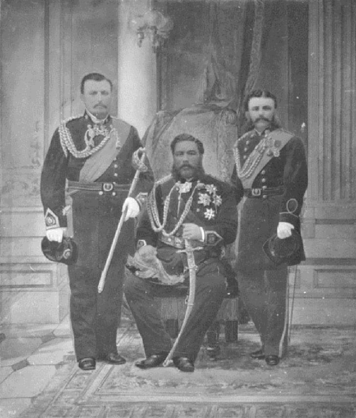 King Kalākaua seated with his aides standing next to him