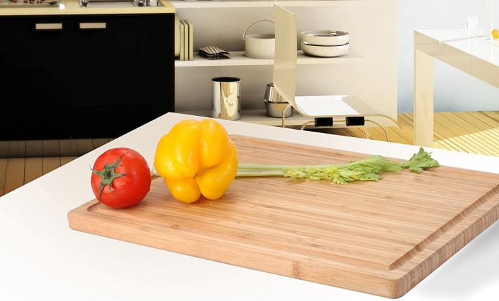 Celery and bell peppers sitting on a wooden cutting board