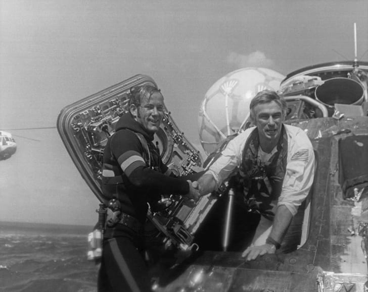 NASA astronaut Eugene Cernan, Commander of the Apollo 17 lunar mission, is welcomed back to Earth by a US Navy Pararescueman, after splashdown in the Pacific Ocean, 19th December 1972