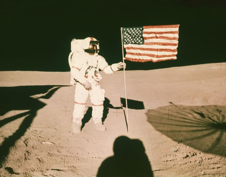 1971: Astronaut Alan B Shepard holds the pole of a US flag on the surface of the moon during the Apollo 14 mission.