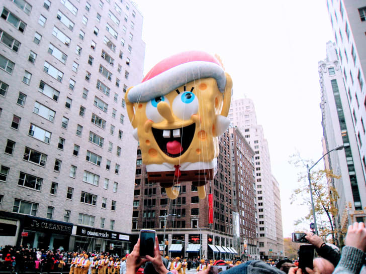 Spongebob Squarepants float, with view of skyscrapers on Sixth Ave and cell phones and marchers, at the Macy's Parade Nov 2016