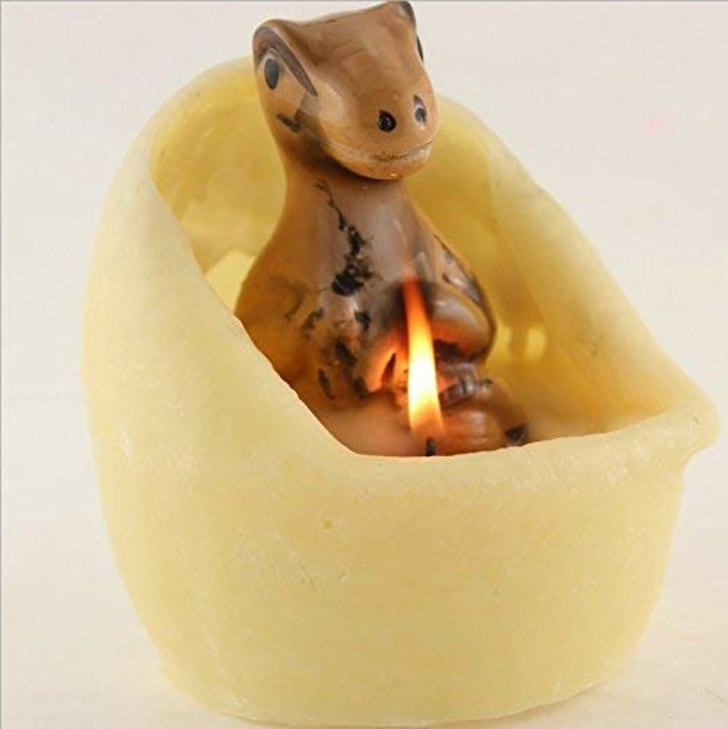 Image of a small brown dinosaur statue sitting in the middle of a cream-colored egg-shaped candle, which has melted around the statue.