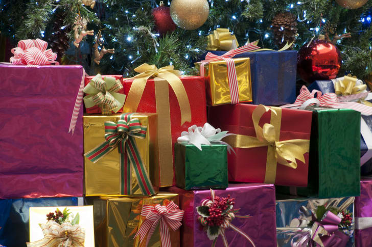 A big pile of brightly wrapped presents next to a Christmas tree.