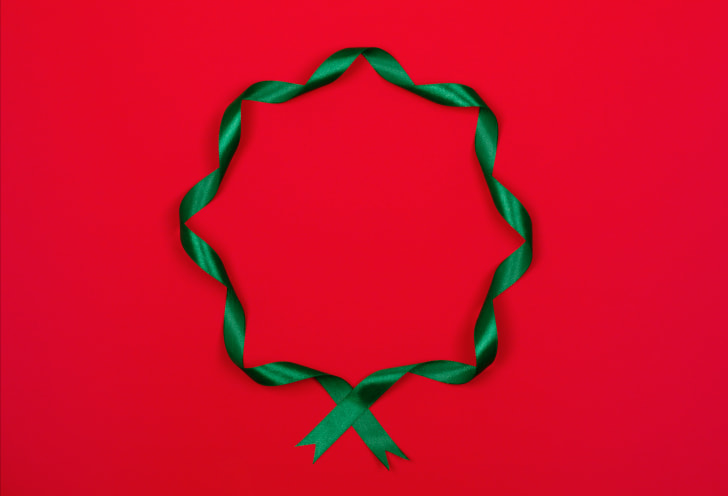 A curly green ribbon in the shape of a wreath on a red background.