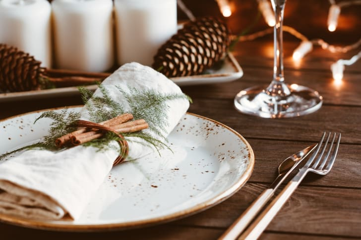 A table set for dinner with a plate topped by a napkin tied with a string that holds two cinnamon sticks and a sprig of a tree to the napkin. A pinecone is in the background.