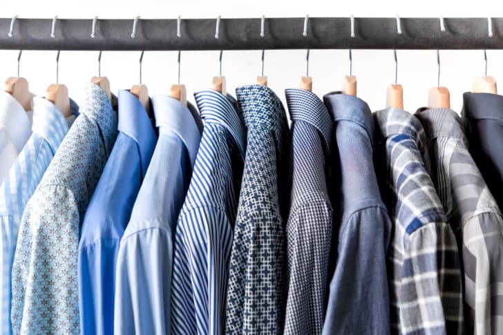 Row of men's shirts in blue colors on hanger
