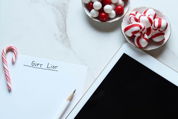 "A blank piece of paper labeled ""gift list"" surrounded by an iPad and candy."