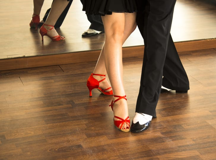 The legs and feet of a man and woman taking a dance class.