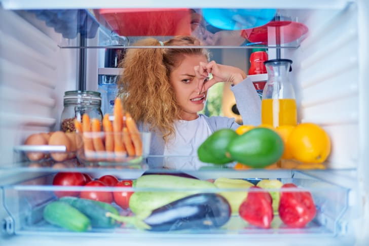 Woman standing in front of opened fridge pinching her nose