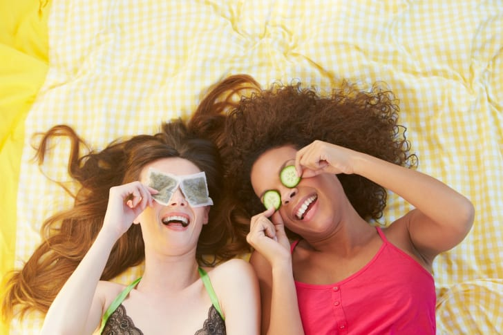 Two women, one with tea bags on her eyes, the other with cucumber slices on her eyes