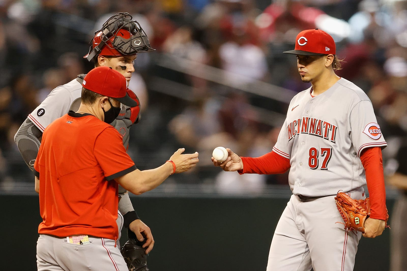 Starting pitcher Jose De Leon #87 of the Cincinnati Reds gives the baseball to manager David Bell #25 during the fifth inning.