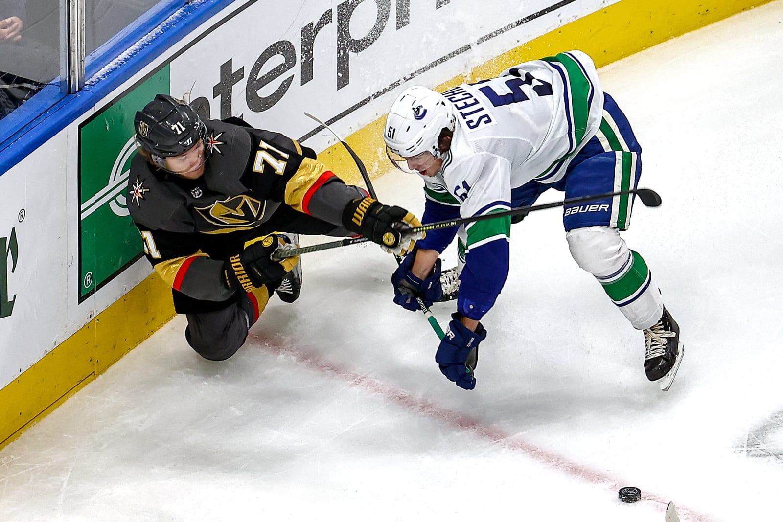 William Karlsson #71 of the Vegas Golden Knights battles for the puck with Troy Stecher #51 of the Vancouver Canucks