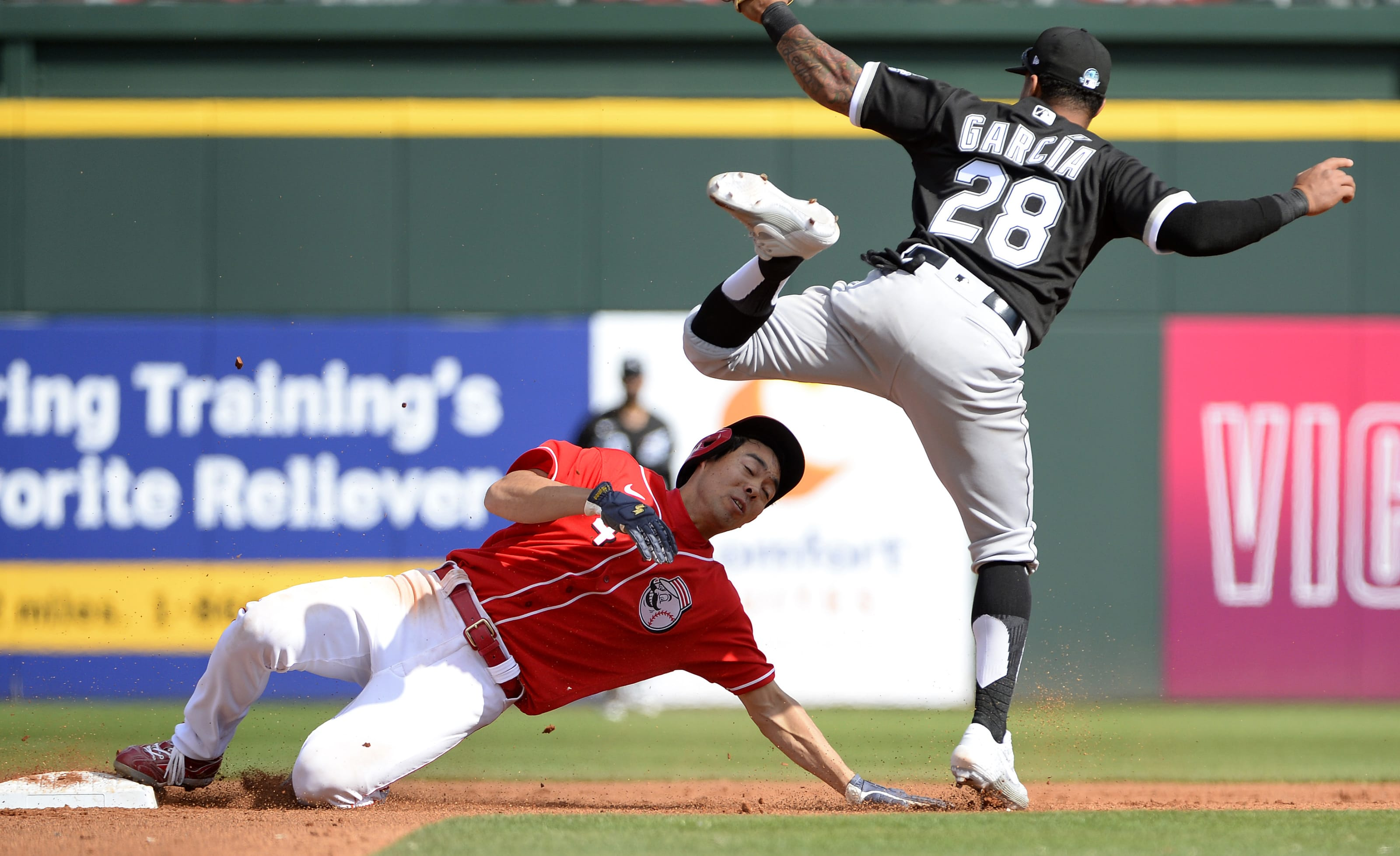 Shogo Akiyama #4 of the Cincinnati Reds is tagged out by Leury Garcia #28 of the Chicago White Sox.