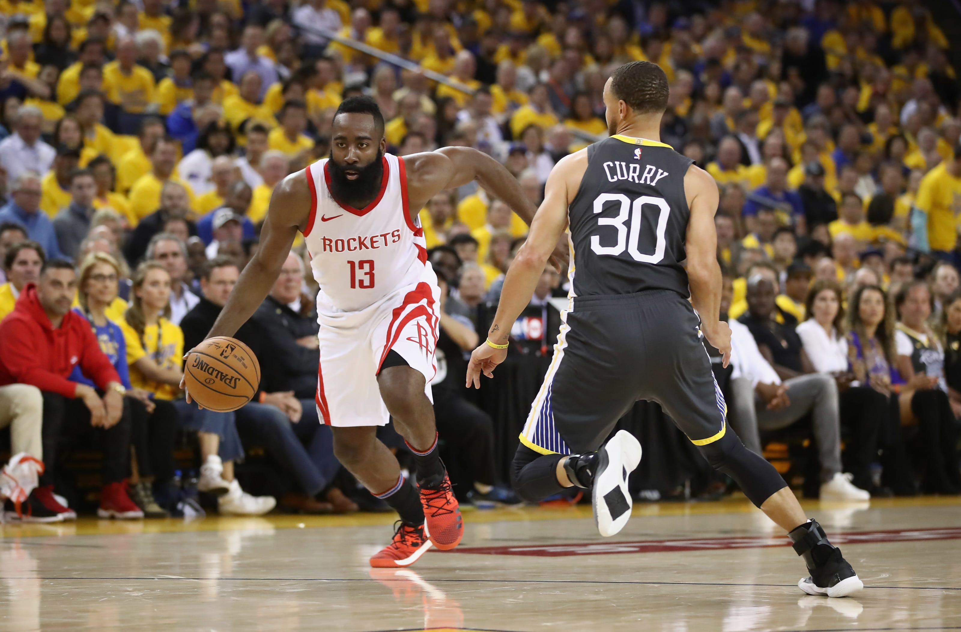 James Harden #13 of the Houston Rockets is guarded by Stephen Curry #30 of the Golden State Warriors