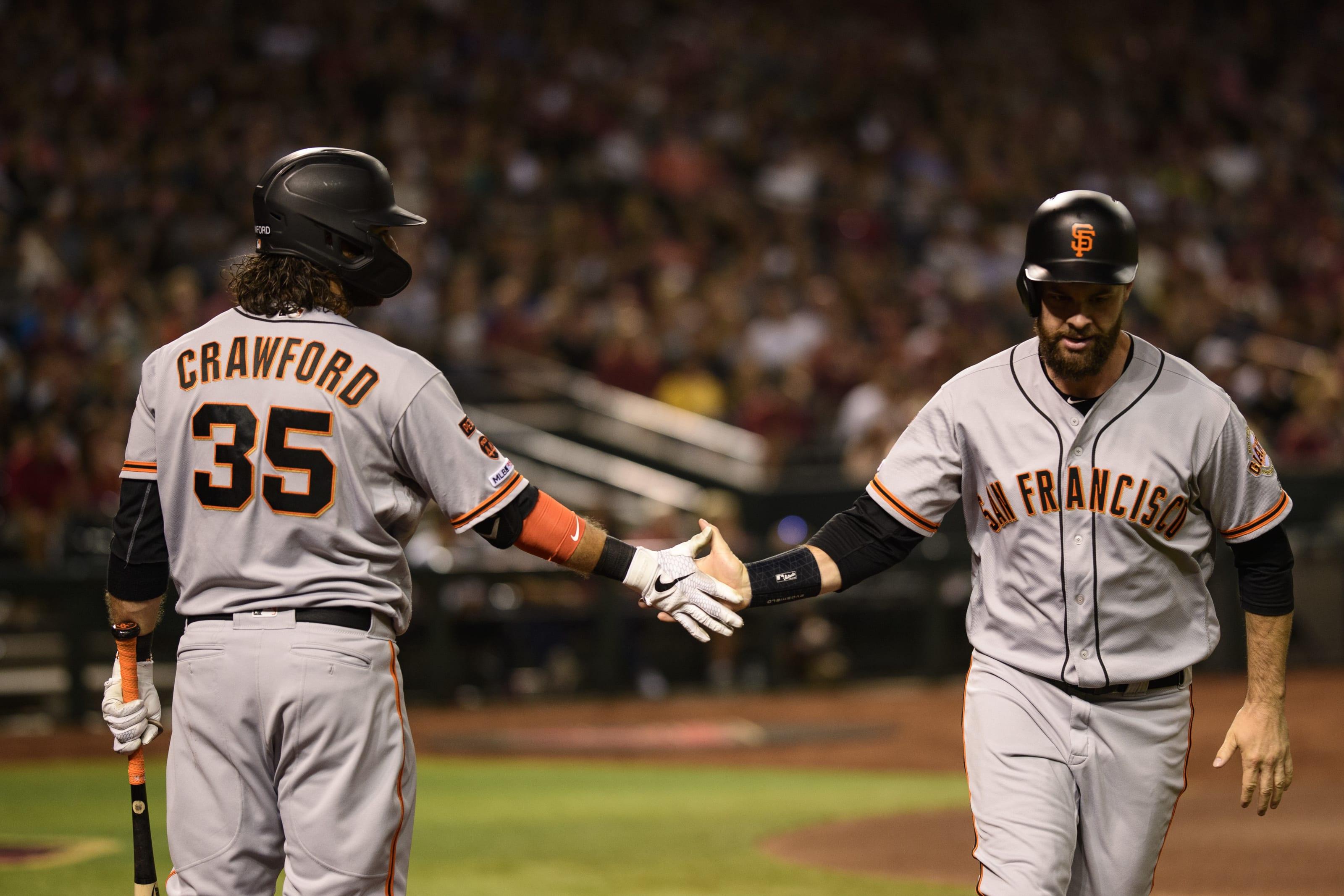 San Francisco Giants Brandon Crawford and Brandon Belt slap hands.
