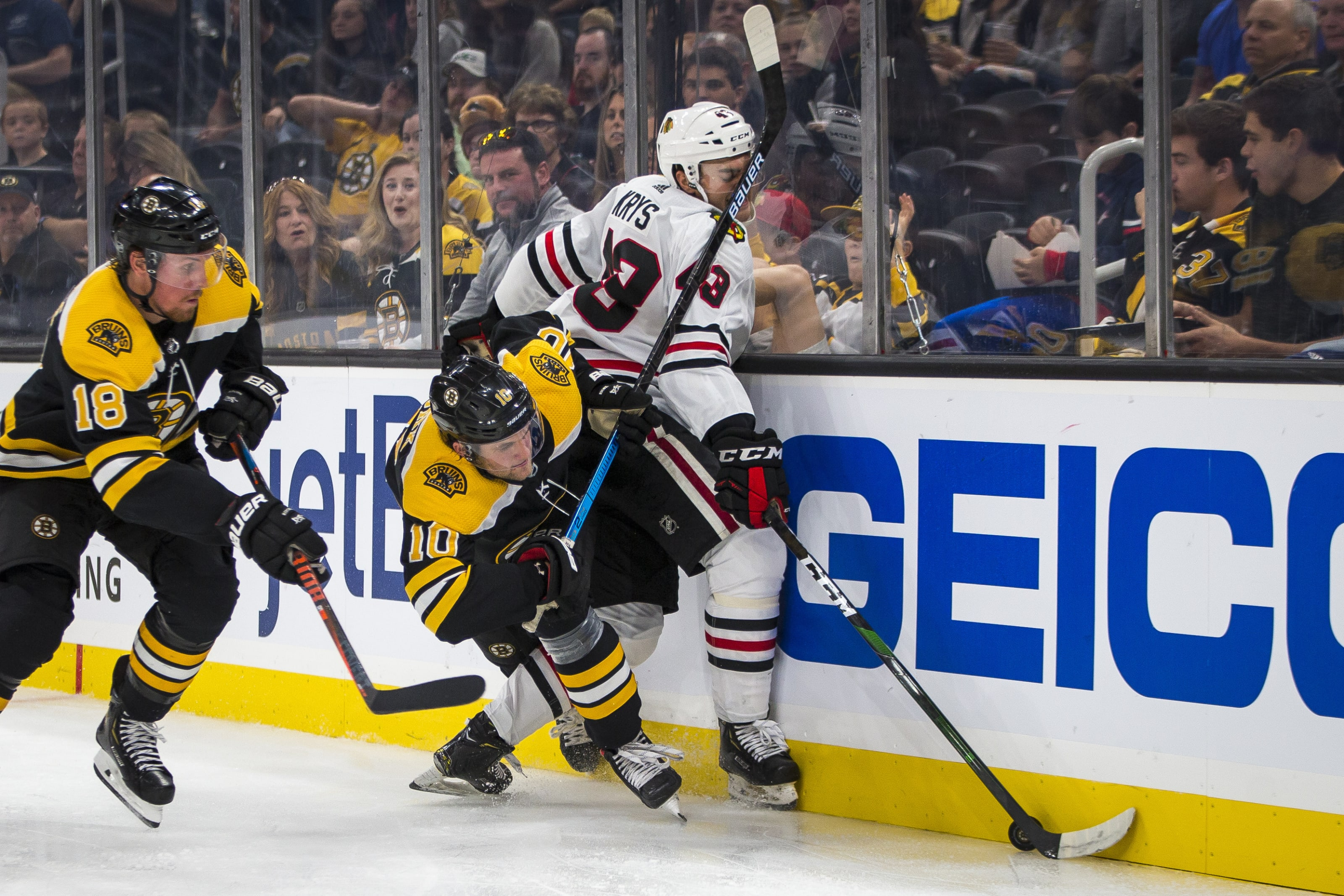 BOSTON - SEPTEMBER 28: Boston Bruins left wing Anders Bjork (10) and Chicago Blackhawks defenseman Chad Krys (43) collide during the second period. The Boston Bruins host the Chicago Blackhawks in their final pre-season NHL hockey game at TD Garden in Boston on Sep. 28, 2019. (Photo by Nic Antaya for The Boston Globe via Getty Images)