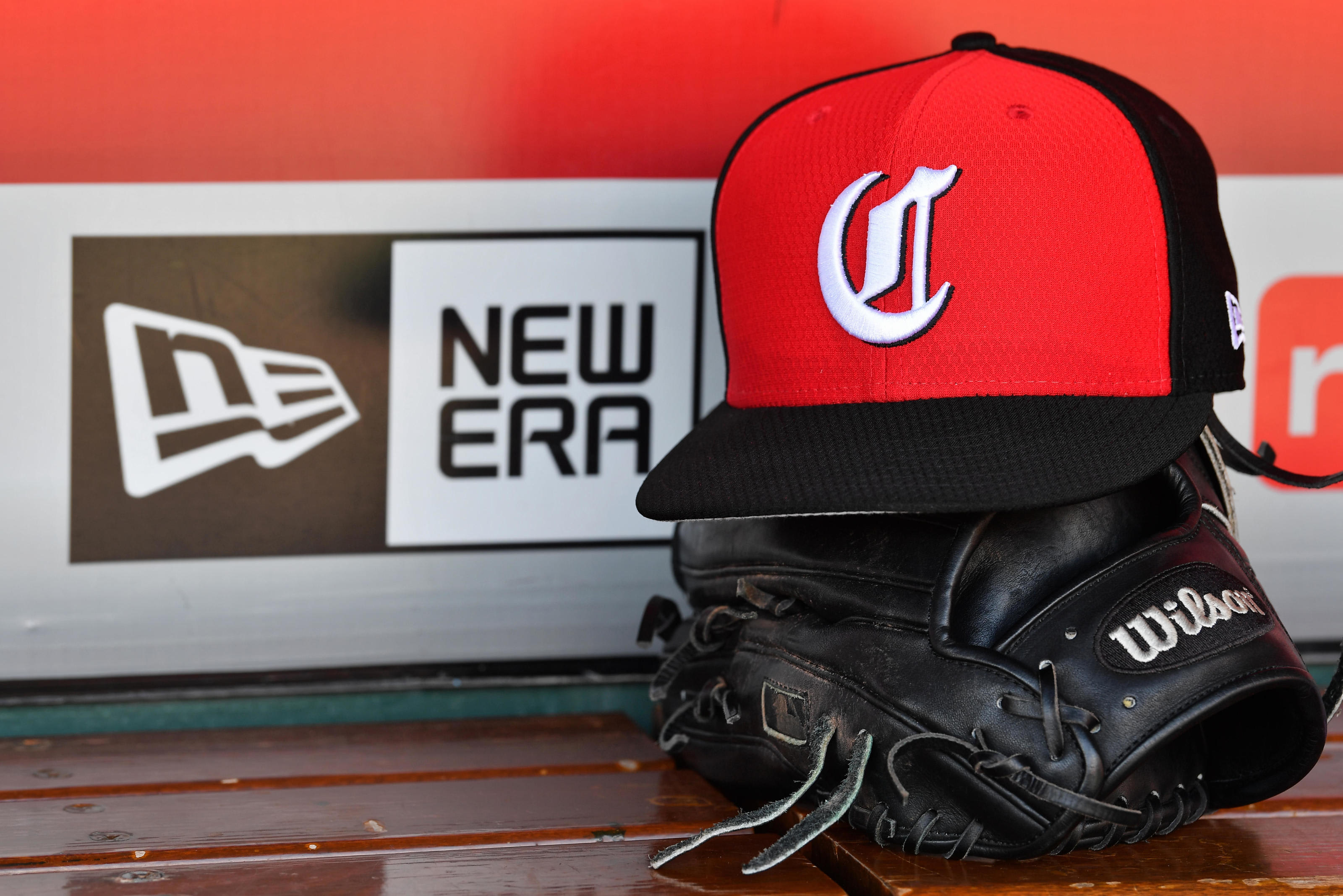 A close up view of a hat and baseball glove in the dugout with the New Era logo before a game between the Cincinnati Reds and the Chicago Cubs