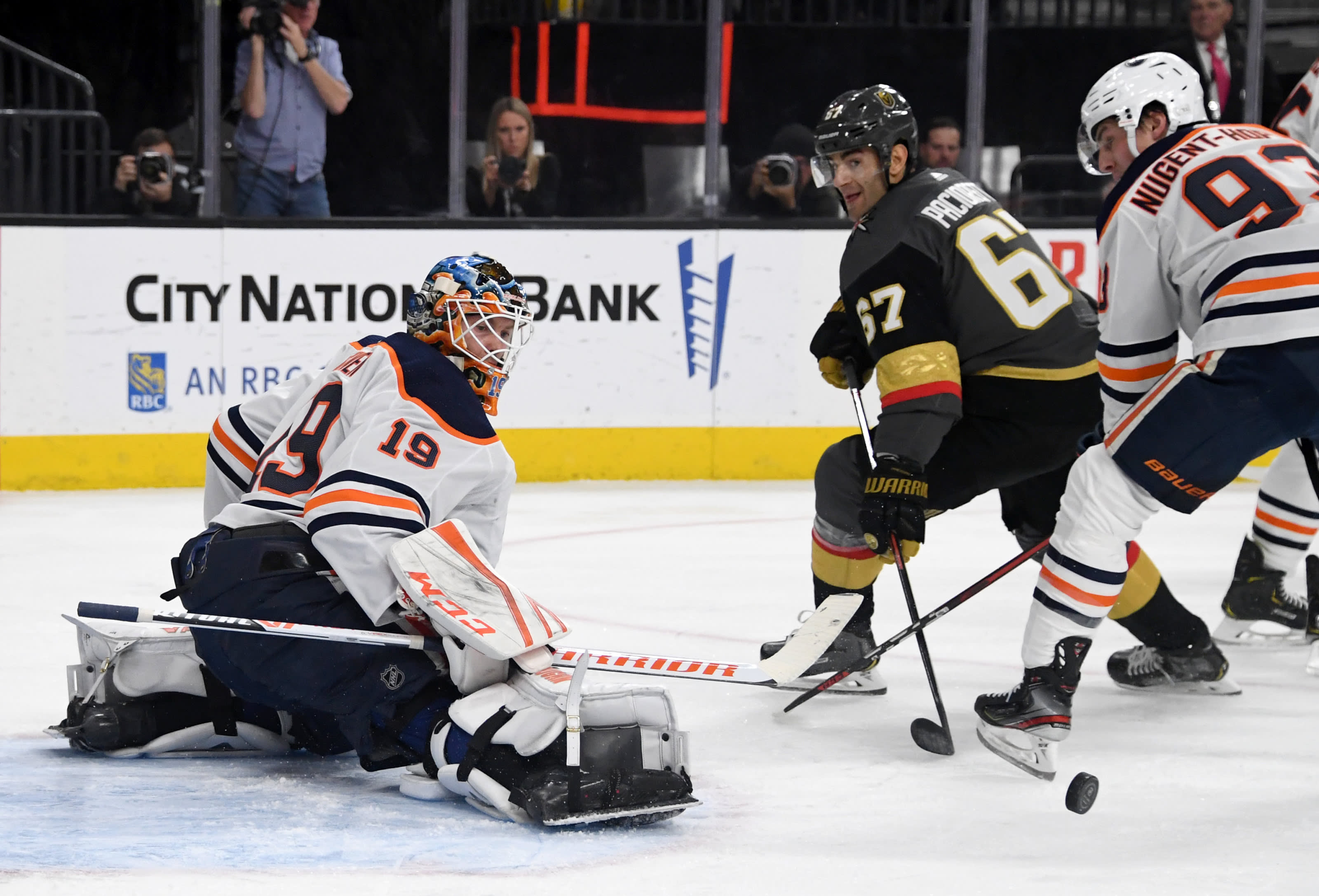 Mikko Koskinen #19 of the Edmonton Oilers makes a save as Max Pacioretty #67 of the Vegas Golden Knights looks for a rebound.