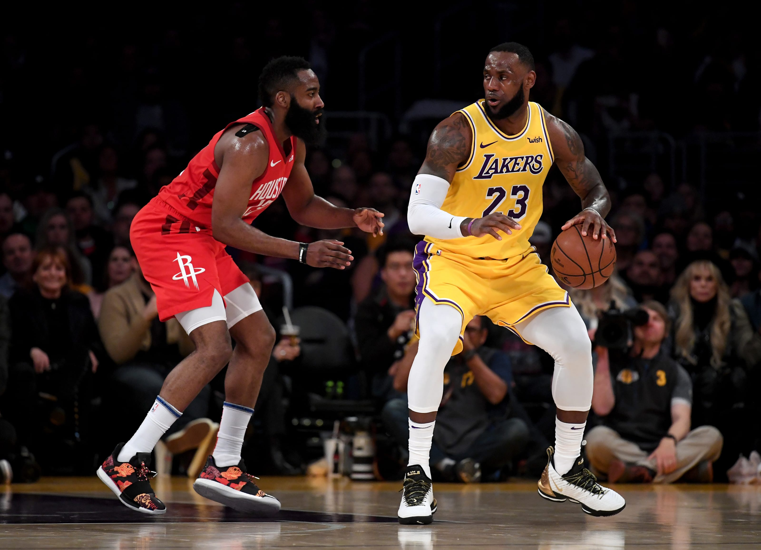 LeBron James #23 of the Los Angeles Lakers backs in on James Harden #13 of the Houston Rockets