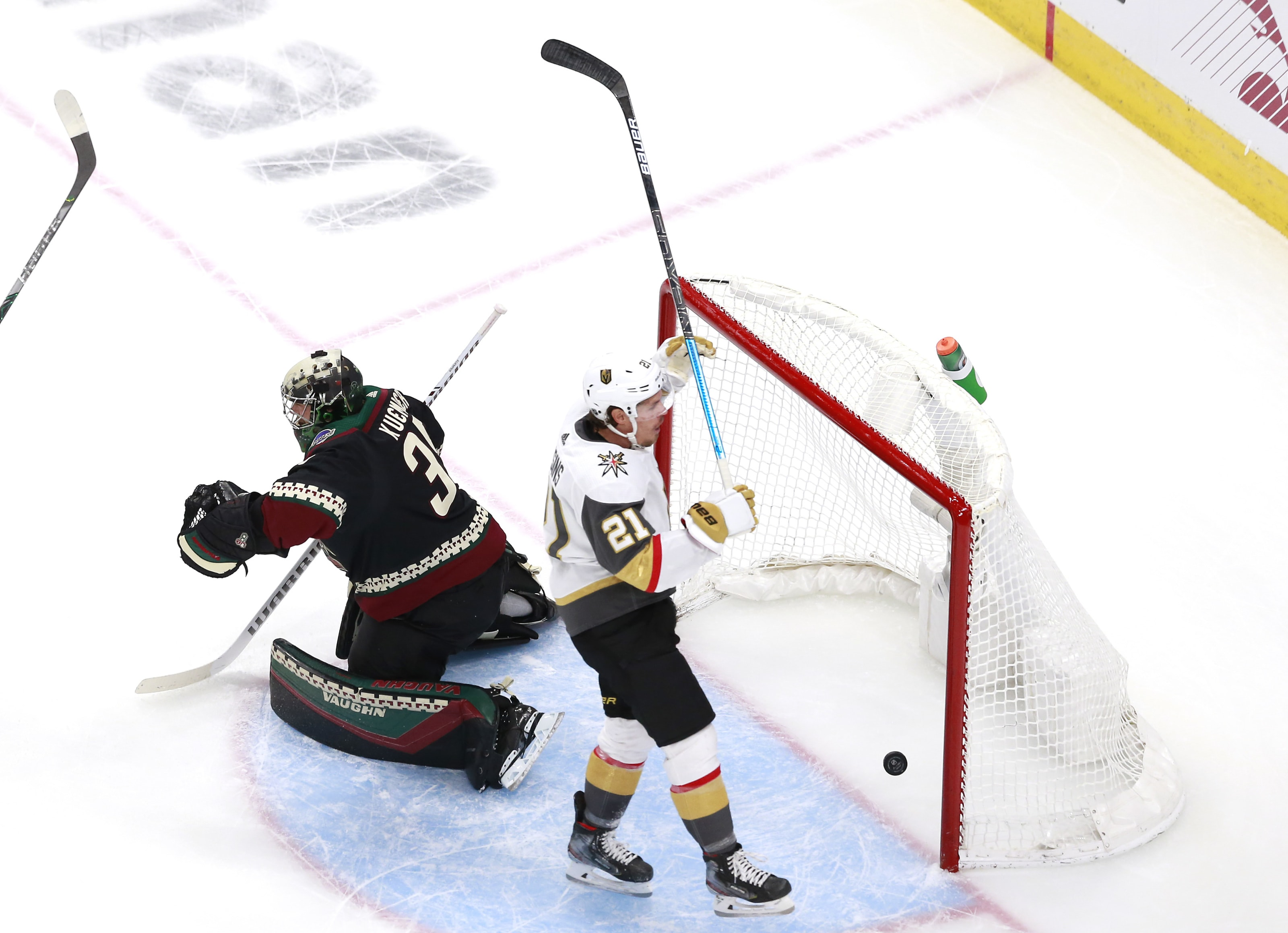 Darcy Kuemper #35 of the Arizona Coyotes is unable to stop a power play goal by Reilly Smith of the Vegas Golden Knights as Nick Cousins #21 of the Vegas Golden Knights celebrates.