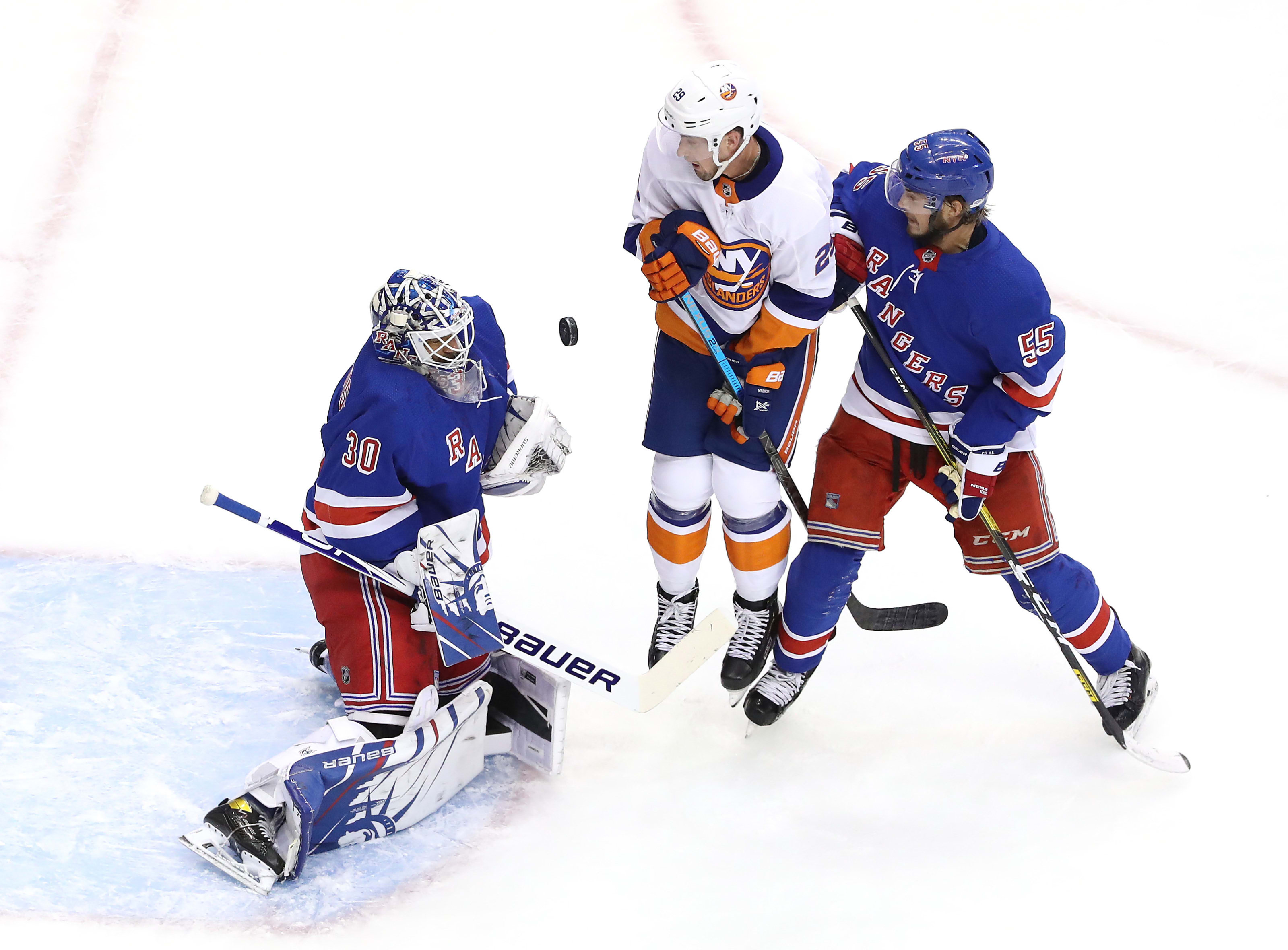 Henrik Lundqvist #30 of the New York Rangers stops a shot in the second period as Brock Nelson #29 of the New York Islanders and Ryan Lindgren #55 of the New York Rangers stand by during an exhibition game
