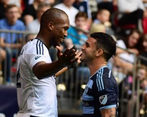Jul 12, 2015; Vancouver, British Columbia, CAN; Vancouver Whitecaps defender Kendall Watson (4) exchanges words with Sporting KC forward Dom Dwyer (14) during the first half at BC Place. Mandatory Credit: Anne-Marie Sorvin-USA TODAY Sports