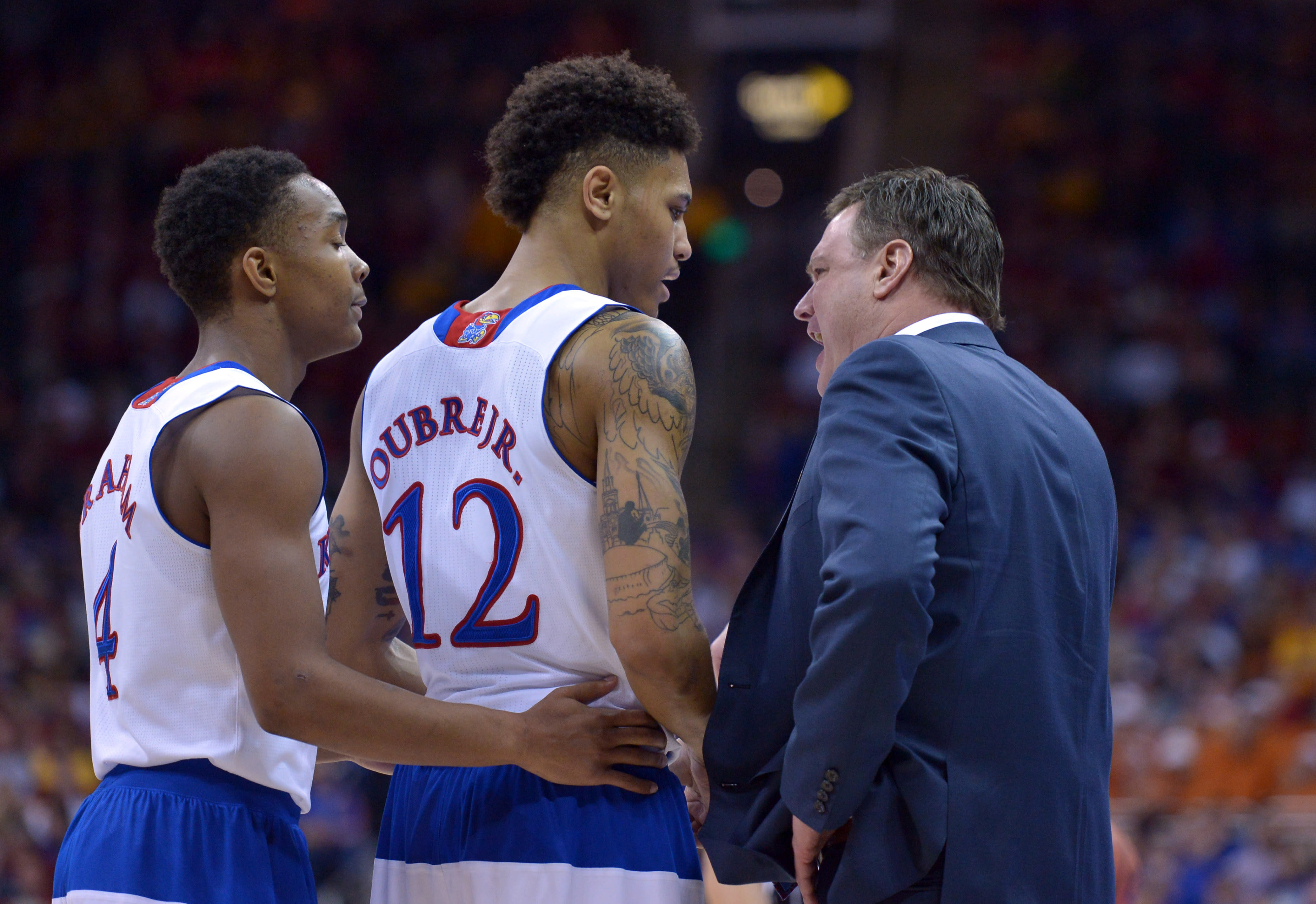 Mar 13, 2015; Kansas City, MO, USA; Kansas Jayhawks head coach Bill Self talks with guard Devonte Graham (4) and guard Kelly Oubre Jr. (12) in a time out of the game against the Baylor Bears during the semifinals round of the Big 12 Championship at Sprint Center. Kansas won 62-52. Mandatory Credit: Denny Medley-USA TODAY Sports