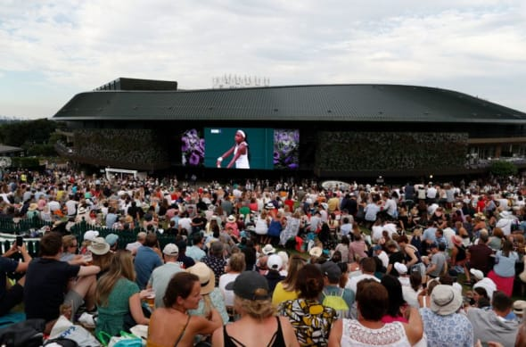 Spectators on Murray Mount (Henman Hill) watch a big screen showing US player Cori Gauff playing against Slovenia's Polona Hercog during their women's singles third round match on the fifth day of the 2019 Wimbledon Championships at The All England Lawn Tennis Club in Wimbledon, southwest London, on July 5, 2019. (Photo by Adrian DENNIS / AFP) / RESTRICTED TO EDITORIAL USE (Photo credit should read ADRIAN DENNIS/AFP via Getty Images)