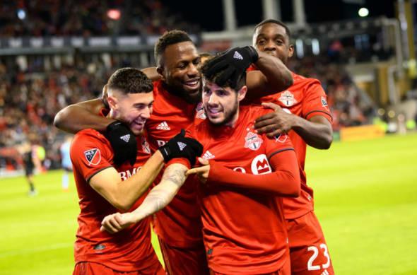 Toronto FC, Jonathan Osorio, Jozy Altidore, Alejandro Pozuelo and Chris Mavinga embrace after a Toronto FC goal. Pozuelo points to his right arm.