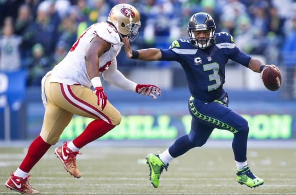 Nov 22, 2015; Seattle, WA, USA; Seattle Seahawks quarterback Russell Wilson (3) stiff-arms away from San Francisco 49ers defensive end Tony Jerod-Eddie (63) during the second quarter at CenturyLink Field. Mandatory Credit: Joe Nicholson-USA TODAY Sports