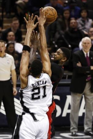 Mar 10, 2015; San Antonio, TX, USA; Toronto Raptors power forward Amir Johnson (behind) shoots the ball over San Antonio Spurs power forward Tim Duncan (21) during the second half at AT&T Center. Mandatory Credit: Soobum Im-USA TODAY Sports